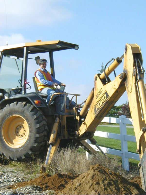 Public Works employee operates a backhoe