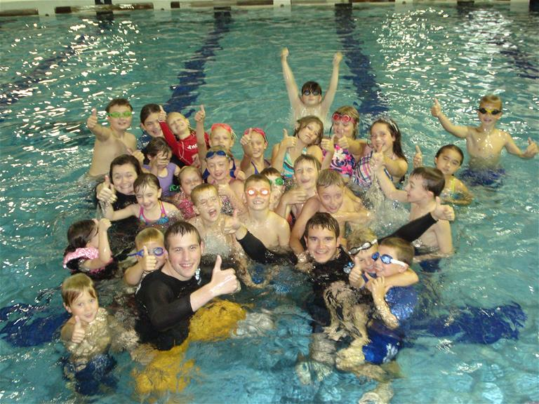 Children gather together to get a picture in the pool