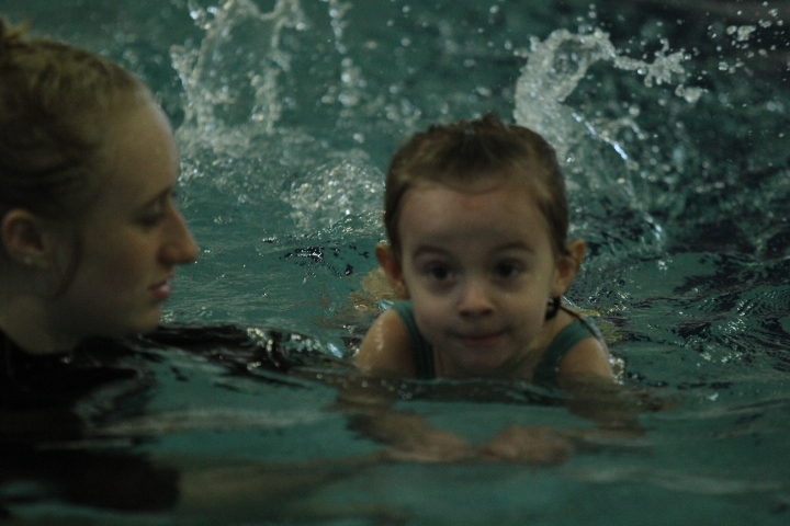 Child learns how to swim with the instructor