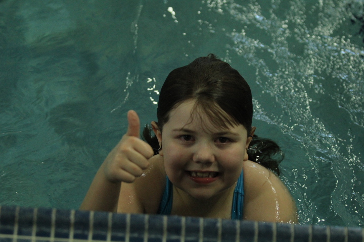 Girl gives the camera a thumbs up from the pool
