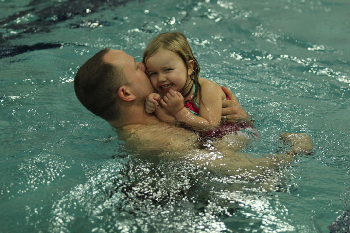 Girl swims in the pool with her father
