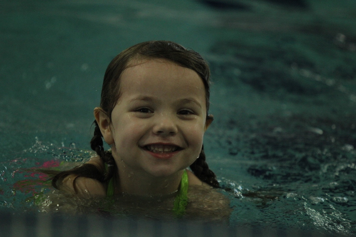 Girl smiles to the camera from the pool