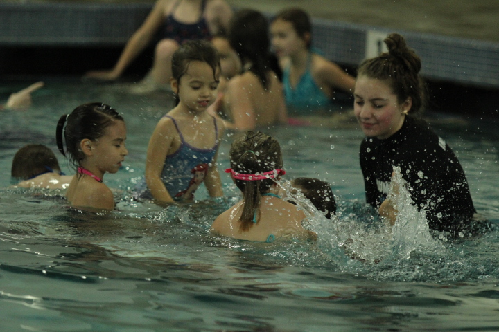 Swim instructor teaches children how to use their legs to swim