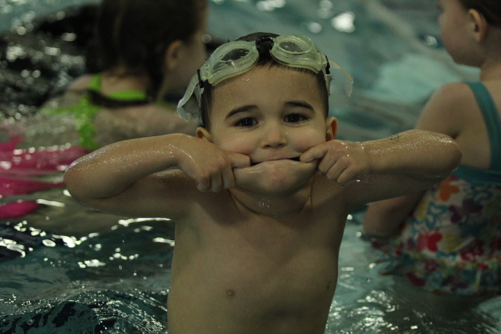A young boy makes a silly face in the pool