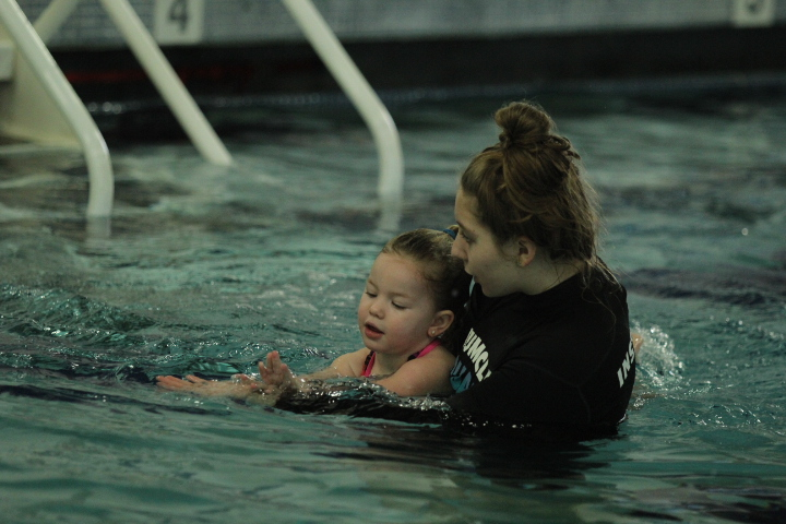 A swim instructor helps teach a child to swim