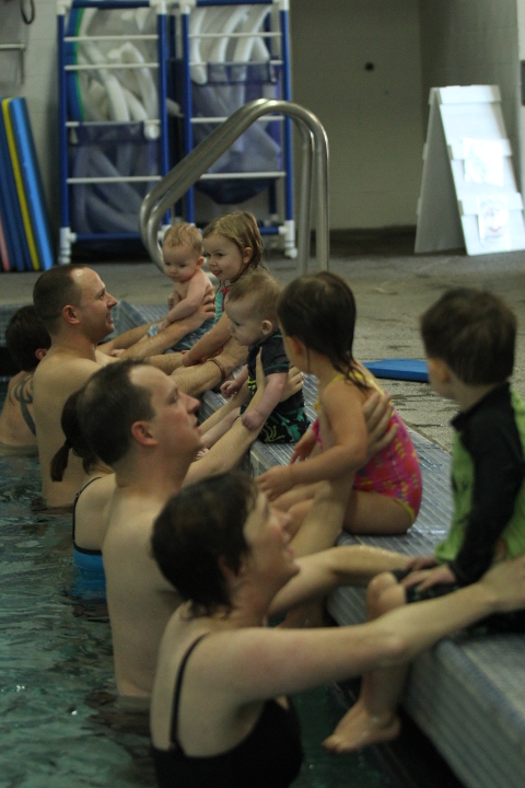 Parents help their children into the pool