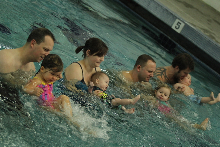 Parents help teach their children to swim