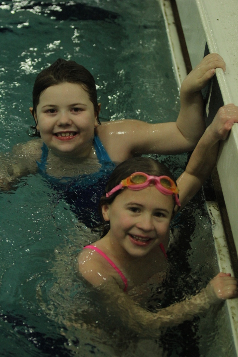 2 girls smile for the camera from the pool