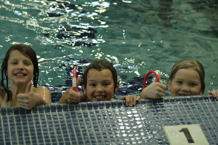 Kids give the camera a thumbs up from the pool