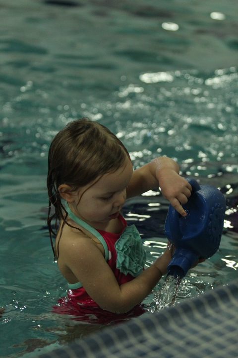 Little girl plays with a watering can in the swimming pool